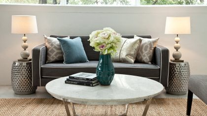 White flowers on marble coffee table, couch with teal pillows, property styling shot